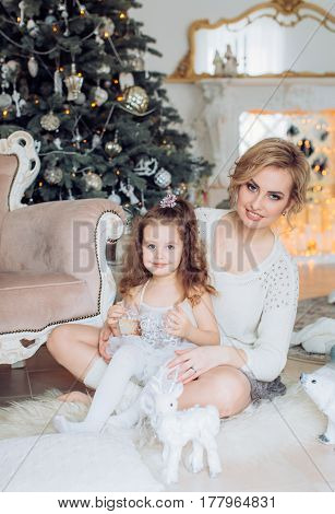 Beautiful young mother with your little daughter near Christmas tree