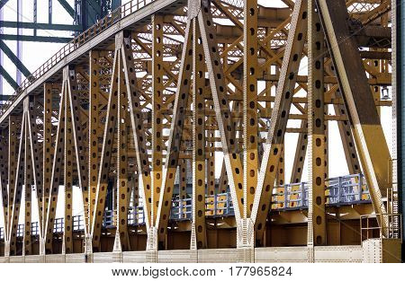 Close angled view of orange metal lift bridge detail in beams and steel construction