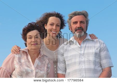 family of adult woman and her parents embracing and smiling, blue sky