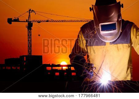 Welding worker welding steel structure with construction crane and building at construction site on sunset for construction industrial work concept