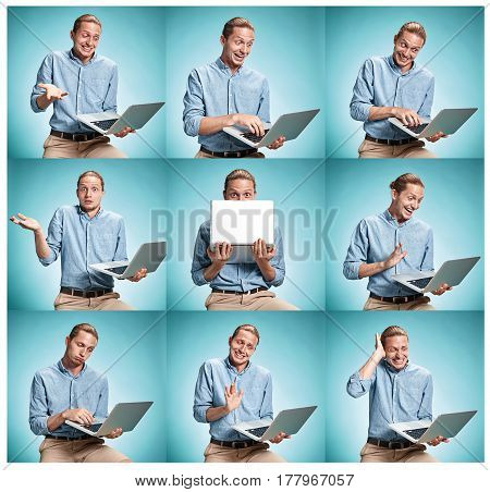 The smiling young man in a blue shirt working on laptop on blue studio backgroundin