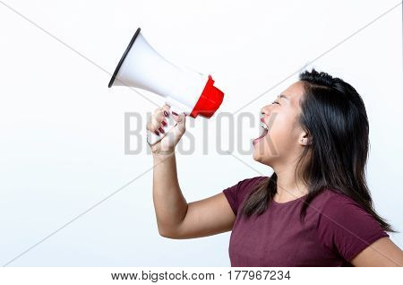 Young woman shouting into a megaphone side view on white conceptual of a rally or protest