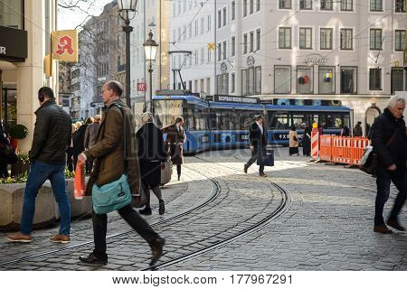 Munich,Germany,March 23,2017:A streetcar approaches as people cross the tracks in a sunny spring afternoon