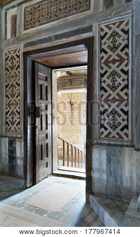 Cairo, Egypt - March 25, 2017: Wooden aged ornate opened door leading to a passage with bright light color decorated marble wall and marble floor, Qalawun Complex, El Moez Street, Medieval Cairo, Egypt