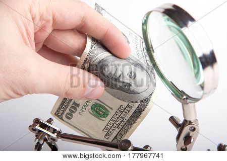 Finance inspector. Checks money for authenticity through a magnifying glass. Hands close-up.