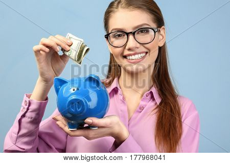 Beautiful young woman putting money into piggy bank, on color background