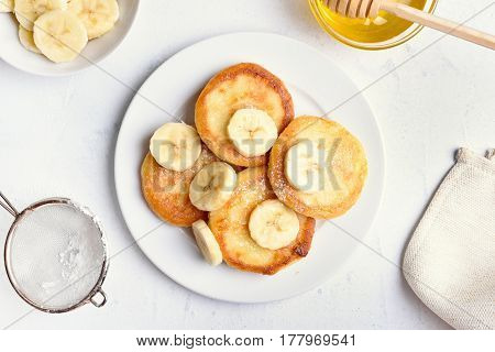 Cottage cheese pancakes with banana slices on plate top view