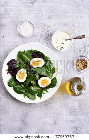 Healthy mix salad with eggs and greens on light stone background top view