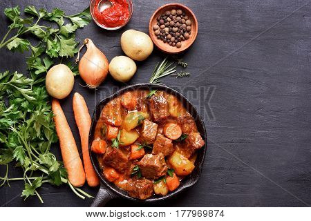 Beef stew in cast iron pan and ingredients on dark background with copy space top view