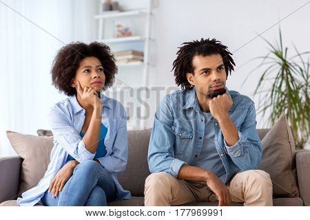 relations, communication and people concept - happy couple sitting on sofa at home