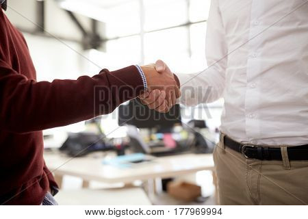business, people, gesture, cooperation and partnership concept - businessmen making handshake at office