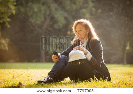 Senior woman engineer looking to phone and relaxing outdoor in park during lunch break