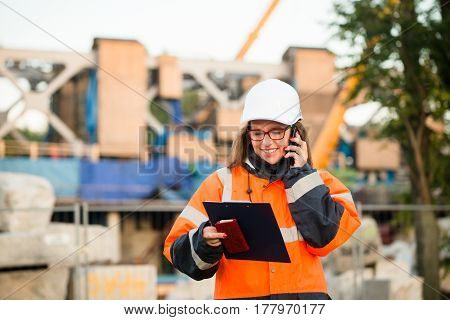 Senior woman engineer wearing protective workwear at work on phone