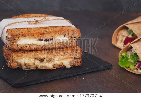 Sandwiches wrapped in paper and tortilla wraps.  Macro, selective focus, blank space.
