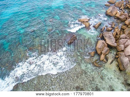 Seychelles Island La Digue aerial top view of a coastline with turquoise sea and granite rocks
