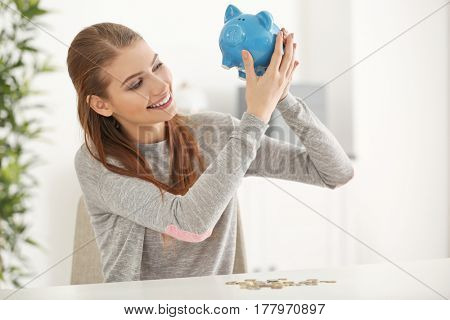 Beautiful young woman with piggy bank and coins at home