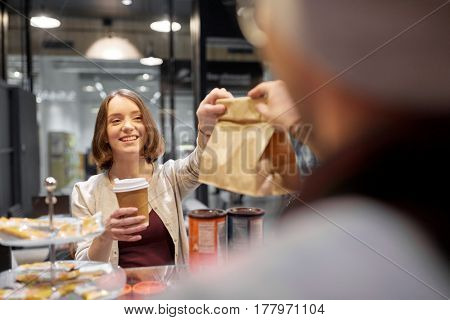 small business, takeaway food, people and service concept - happy female customer with coffee cup taking paper bag from man or barman at vegan cafe