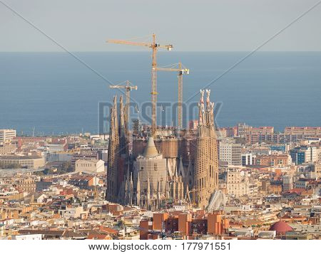 Barcelona - 9 October 2015: The Catholic Cathedral of the Sagrada Familia and the blue sea in the distance a top view of 9 October 2015 Barcelona ​​Spain