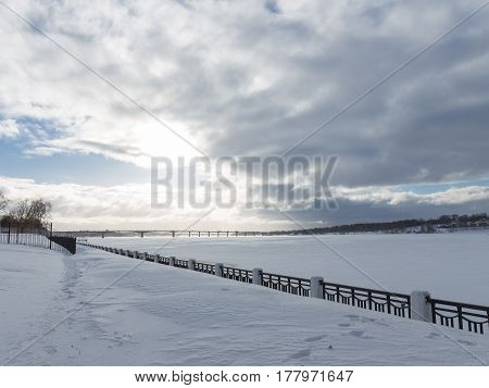 Kostroma - February 15 2017: Beautiful embankment of a large frozen river Volga a lot of snow in the winter and a bridge in the distance February 15 2017 Kostoma Korstromskaya oblast Russia