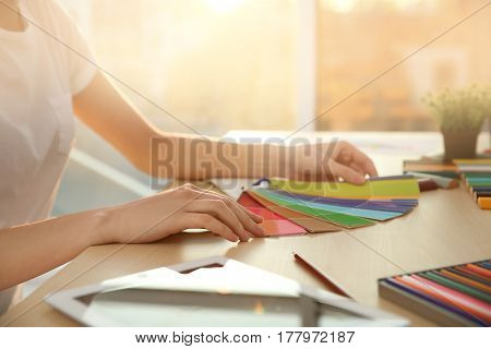 Young female decorator working in office