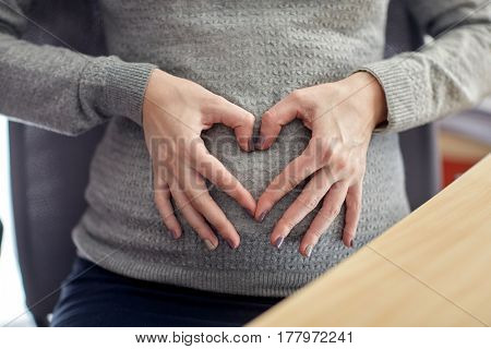 pregnancy, business, work and people concept - pregnant businesswoman making heart shape at office