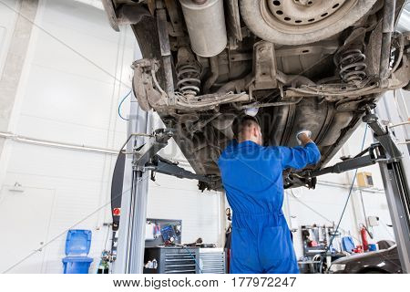 service, repair, maintenance and people concept - auto mechanic man or smith repairing car at workshop