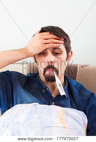 Sick Man with Thermometer on the Sofa at the Home