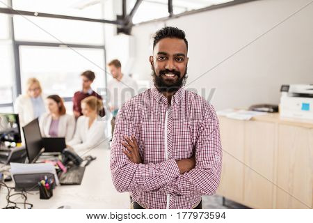 business, corporate, people and teamwork concept - happy indian man over creative team in office