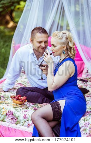 Man and woman sitting on the bed in the lawn and drinking wine from glass and look at each other in Lviv, Ukraine.