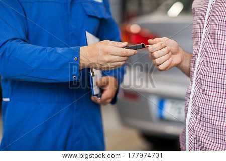 auto service, repair, maintenance and people concept - mechanic giving car key to man or owner at workshop