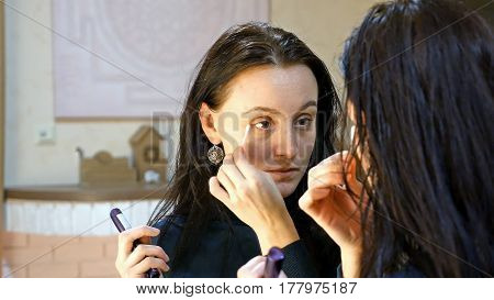 Beautiful brunette woman with long black silky applies make-up on her eyes and eyelashes in front of mirror in make-up dressing room bathroom or restroom.