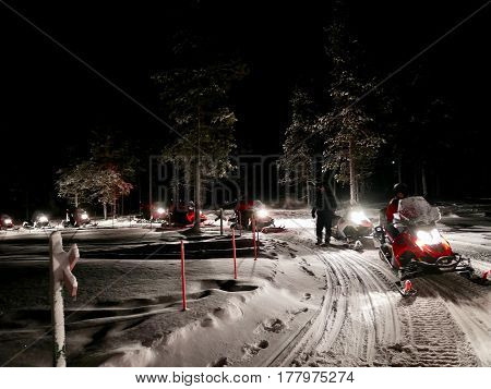 Snowmobile caravan rides in the dark in Finland