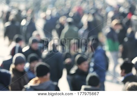 Crowd of people walking on busy city street, blurred view