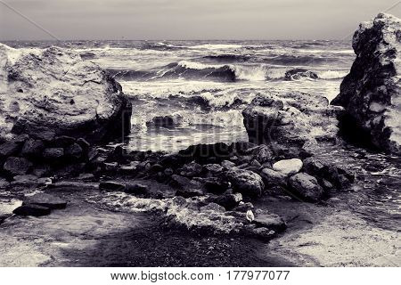 Seascape with large rocks on shore and waves on water. Stormy weather at sea. Toned black and white photo