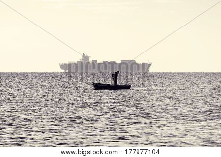 Man and ship. Silhouette of fisher in boat in sea in early morning. Seascape at dawn. Toned black and white photo