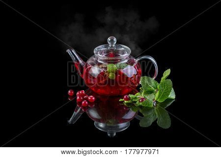 Glass teapot with black tea. Cranberry mint. On a black background with reflection