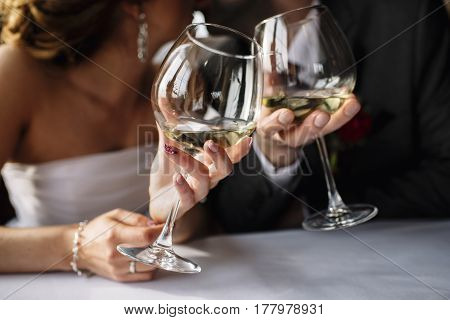 Wedding couple with glasses of wine in hands mark the wedding ceremony in the restaurant at the table. bride and groom with earrings in a dark suit blurred focus only hands and glasses of wine