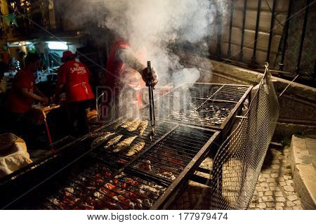 Lisbon Portugal - June 12 2014: Man grilling sardines in a barbecue in a street of the Alfama neighbourhood during the Saint Anthony Feast in Lisbon Portugal