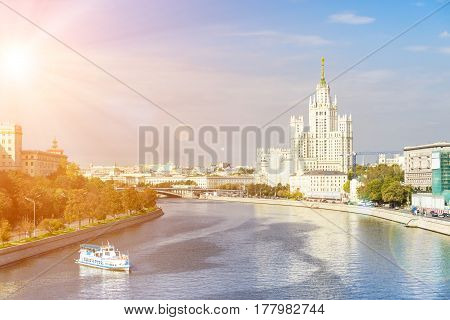 Kotelnicheskaya embankment with leisure boat floating across the Moscow river on a sunny day