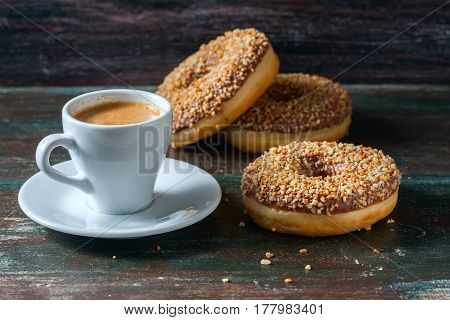 Coffee And Homemade Donuts With Chocolate And Nuts On A Dark Wooden Background.