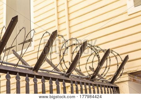 Coils of Razor Wire by a House