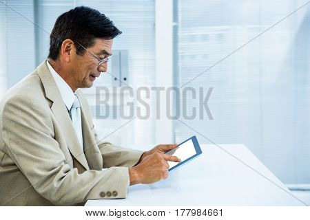 Smiling asian businessman using tablet in office