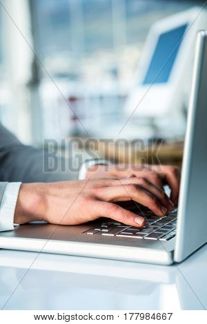 Busy businesswoman typing on computer in office