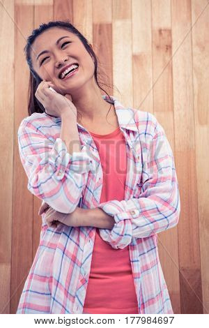 Happy Asian woman on phone call against wooden wall