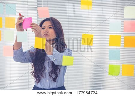 Asian businesswoman using sticky notes on wall in office
