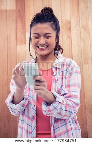 Happy Asian woman using smartphone against wooden wall