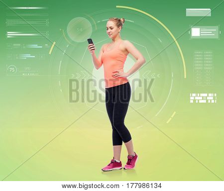sport, fitness, technology and people concept - happy smiling sportive young woman with smartphone over green background