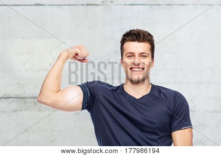 sport, fitness, power, strength and people concept - happy sportive man showing bicep over concrete wall background