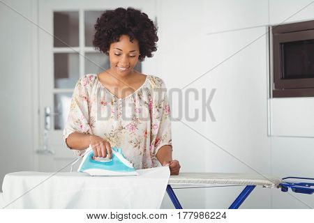 Smiling woman ironing in the kitchen at home