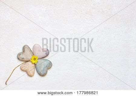 four-leaved clover made of soapstone hearts and textured beige background and copy space